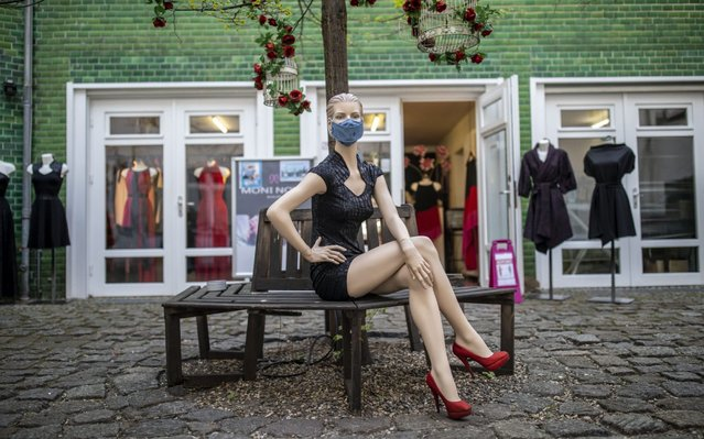 A store mannequin with a protective mask stands before a clothes store as they open for the first time since March during the novel coronavirus (COVID-19) pandemic on April 22, 2020 in Berlin, Germany. Small to midsized-shops are opening across Germany this week as state authorities follow a recommendation by the federal government to ease restrictions imposed in March meant to slow the spread of the coronavirus. Some schools are also planning to reopen soon, as are museums and hair salons in coming weeks. (Photo by Maja Hitij/Getty Images)