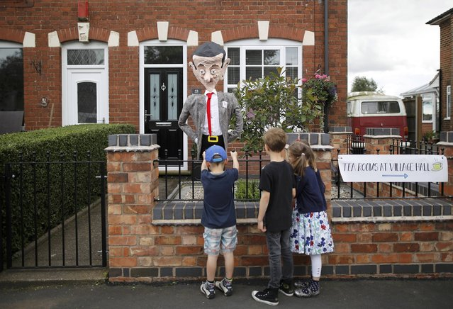Children look at a scarecrow depicting the film character Mr Bean during the Scarecrow Festival in Heather, Britain July 31, 2016. (Photo by Darren Staples/Reuters)