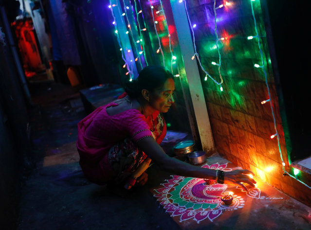 A woman decorates her house on the eve of the Hindu festival of Diwali in a slum in Mumbai, October 18, 2017. (Photo by Danish Siddiqui/Reuters)