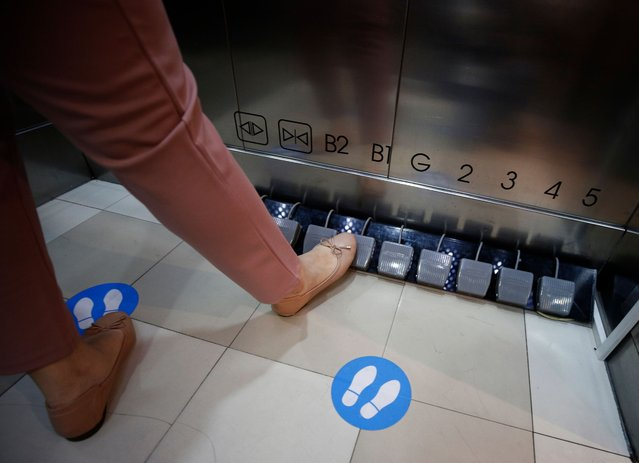 A shopper pushes the pedals of a foot-operated elevator at Seacon Square shopping mall in Bangkok, Thailand, 20 May 2020. The mall installed foot-operated controls for elevators as part of the measures to curb the spread of coronavirus. (Photo by Narong Sangnak/EPA/EFE/Rex Features/Shutterstock)