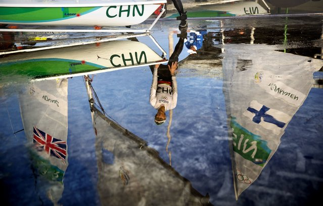 China's Xu Lijia is reflected in a puddle as she hoses off her boat after competing in the Laser Radial women sailing race at the 2016 Summer Olympics in Rio de Janeiro, Brazil, Tuesday, August 9, 2016. (Photo by David Goldman/AP Photo)