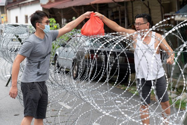 A man collect supplies over barbed wire in the coronavirus locked down area of Selayang Baru, outside of Kuala Lumpur, Malaysia, on Sunday, April 26, 2020. The lockdown was implemented to allow authorities to carry out screenings to help curb the spread of coronavirus. (Photo by Vincent Thian/AP Photo)