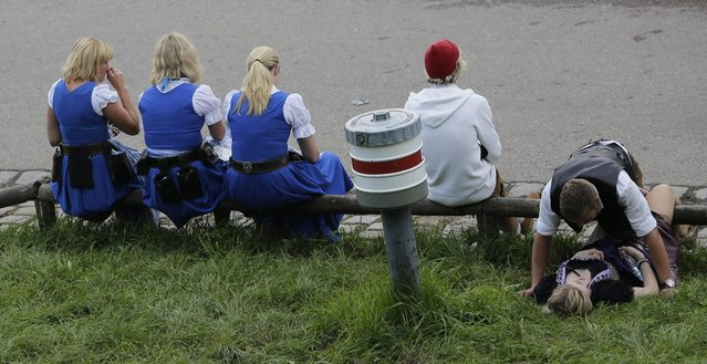 Waitresses rest besides visitors on a meadow on the opening day of the 181st Oktoberfest beer festival in Munich, southern Germany, Saturday, September 20, 2014. (Photo by Matthias Schrader/AP Photo)