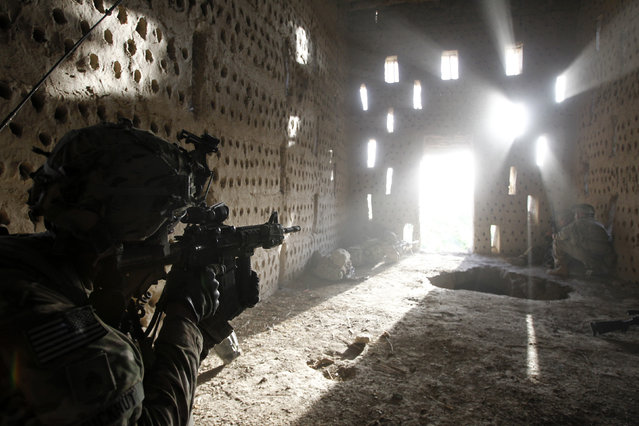 U.S. soldier Nicholas Dickhut from 5-20 infantry Regiment attached to 82nd Airborne points his rifle at a doorway after coming under fire by the Taliban while on patrol in Zharay district in Kandahar province, southern Afghanistan April 26, 2012. (Photo by Baz Ratner/Reuters)