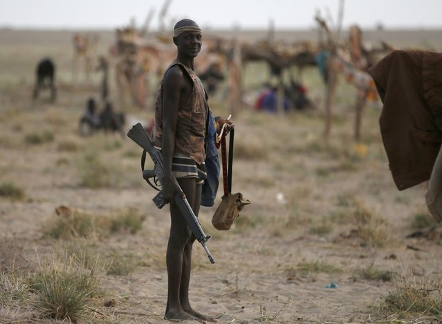 A Turkana man holds a rifle on the western shore of Lake Turkana close to Todonyang near the Kenya-Ethiopia border in northern Kenya September 25, 2014. The Turkana people have historically clashed over ethnic differences and precious resources such as fishing, pasture and fresh water with other tribes bordering their territory, such as the Dassanach from southern Ethiopia. (Photo by Goran Tomasevic/Reuters)
