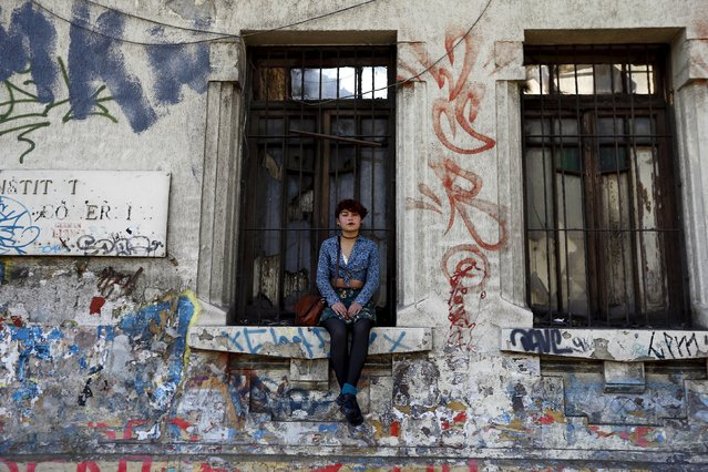 A girl sits on a window ledge as demonstrators march during a protest marking the country's 1973 military coup, in Santiago, Chile September 13, 2015. (Photo by Ivan Alvarado/Reuters)