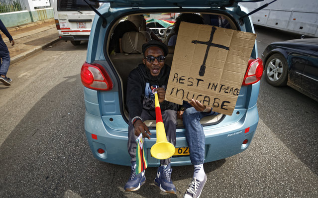 """Protesters demanding President Robert Mugabe stand down ride in the back of a car with a placard """"Rest in peace Mugabe"""" as they drive towards State House in Harare, Zimbabwe Saturday, November 18, 2017. In a euphoric gathering that just days ago would have drawn a police crackdown, crowds marched through Zimbabwe's capital on Saturday to demand the departure of President Robert Mugabe, one of Africa's last remaining liberation leaders, after nearly four decades in power. (Photo by Ben Curtis/AP Photo)"""