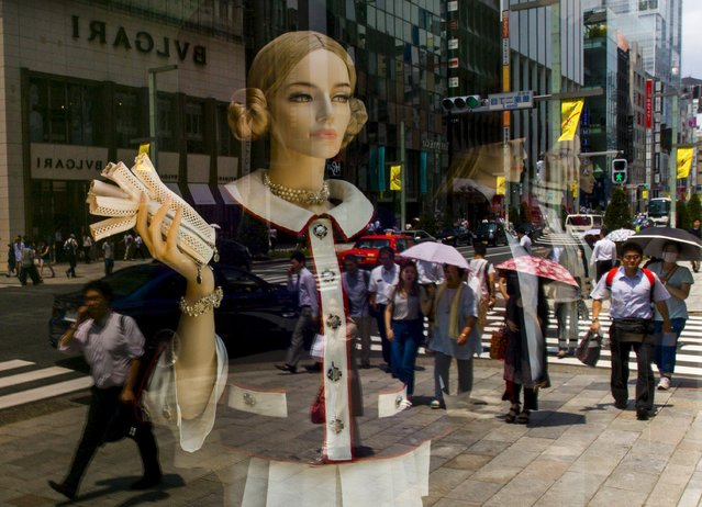 People are reflected in a shop window as they walk along a street in a shopping district in Tokyo, Japan June 25, 2015. (Photo by Thomas Peter/Reuters)