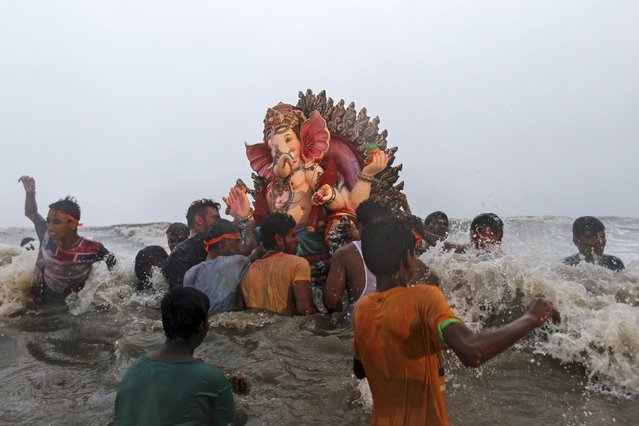 Devotees carry an idol of the Hindu god Ganesh, the deity of prosperity, into the Arabian Sea on the fifth day of the ten-day-long Ganesh Chaturthi festival in Mumbai, India, September 21, 2015. Ganesh idols are taken through the streets in a procession accompanied by dancing and singing, and later immersed in a river or the sea symbolising a ritual seeing-off of his journey towards his abode, taking away with him the misfortunes of all mankind. (Photo by Danish Siddiqui/Reuters)