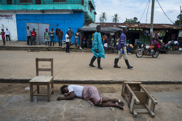 "A woman lays dead outside the Redemption Hospital on Saturday September 20, 2014 in Monrovia, Liberia. Ebola patients come to the hospital, which has become a transfer and holding center to intake Ebola patients, but there is no space and some die while waiting outside. Redemption is located in one of the poorest neighborhoods of Monrovia that locals call ""New Kru Town"". (Photo by Michel du Cille/The Washington Post)"