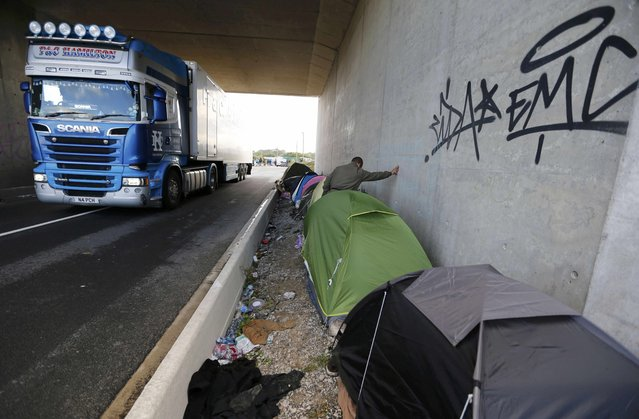 "A migrant stands between a row of tents under a bridge near a highway overpass near the makeshift camp called ""The New Jungle"" in Calais, France, September 19, 2015. (Photo by Regis Duvignau/Reuters)"