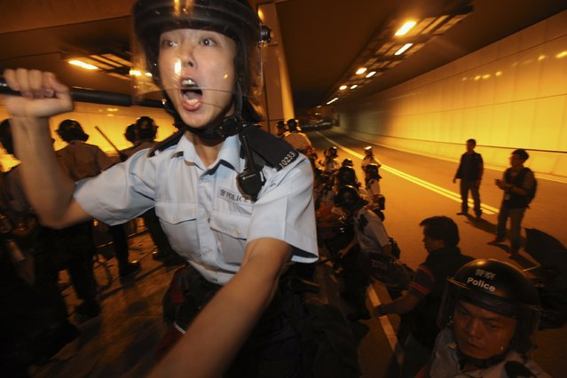 A riot policeman reacts as pro-democracy protesters storm into a vehicle tunnel to block a road leading to the financial Central district in Hong Kong October 14, 2014. Chaotic scenes have broken out in Admiralty late Tuesday as riot police fired pepper spray during clashes with a large number of protesters near the government's headquarters, government radio reported. (Photo by Reuters/Stringer)