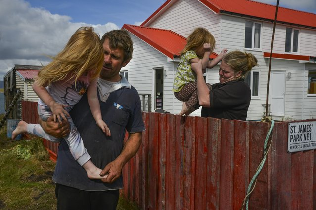 Eden Molkenbuhr, 3, L, is held by her father, Lee Molkenbuhr, as her sister, Charleigh Molkenbuhr, 2, is lifted into their family's yard by their mother, Martha Molkenbuhr, on Friday, February 12, 2016, in Johnson's Harbour Farm, Falkland Islands. (Photo by Jahi Chikwendiu/The Washington Post)