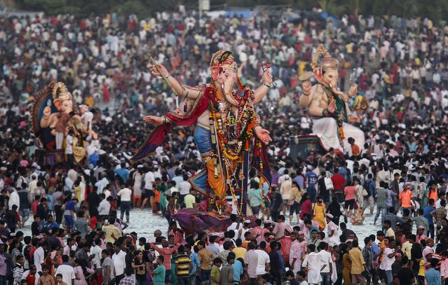 Devotees gather around the idols of Hindu elephant god Ganesh, the deity of prosperity, before they are carried for immersion into the Arabian Sea on the last day of the Ganesh Chaturthi festival in Mumbai, India, September 27, 2015. (Photo by Shailesh Andrade/Reuters)