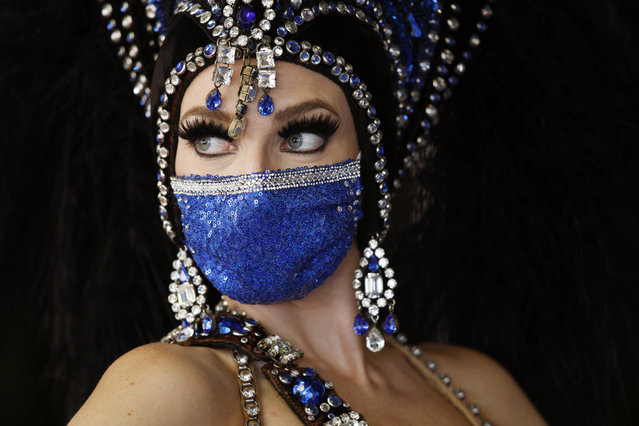 A showgirl in a face mask stands by the door at the reopening of Bally's Las Vegas hotel and casino, Thursday, July 23, 2020, in Las Vegas. The casino reopened for the first time since March following a closure to prevent the spread of the coronavirus. (Photo by John Locher/AP Photo)