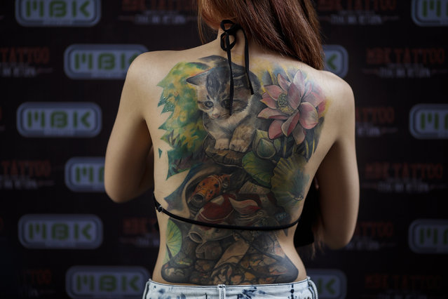 A competitor shows her tattoos at the MBK Tattoo Contest in a shopping mall in Bangkok October 23, 2014. (Photo by Athit Perawongmetha/Reuters)