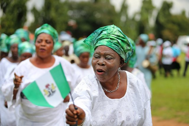 A woman raises the Nigerian flag as she participates in a parade to commemorate Nigeria's 55th Independence Day in Lagos, October 1, 2015.  REUTERS/Akintunde Akinleye