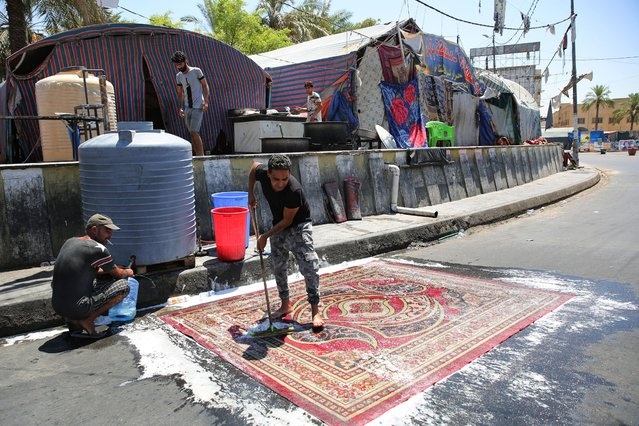 An Iraqi anti-government demonstrator washes a carpet in front of a tent in Tahrir Square in the capital Baghdad, on August 1, 2020. Iraq will hold its next parliamentary elections nearly a year early, the premier announced yesterday, as he seeks to make good on promises he offered when he came to power Protests began in October, with thousands taking to the streets of Baghdad and across the south Demonstrators demanded that the political system be dismantled, pointing to endemic corruption and what many see as the malign influence of sectarian interests. (Photo by Ahmad Al-Rubaye/AFP Photo)