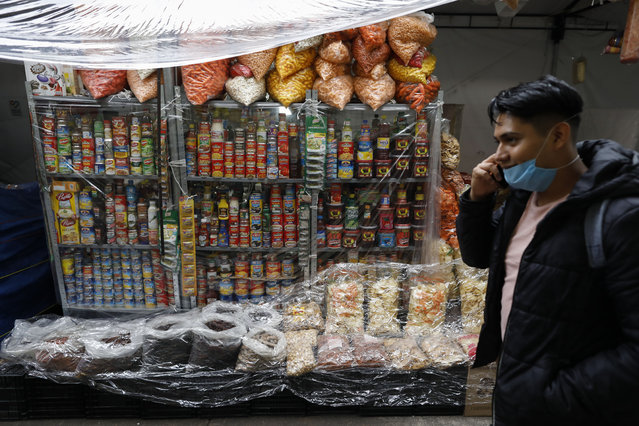 A man walks past goods covered in plastic to protect against possible rain, at Mercado San Cosme, where some vendors decided to put in place protective measures against coronavirus while others continue to work without masks or barriers, in Mexico City, Thursday, June 25, 2020. (Photo by Rebecca Blackwell/AP Photo)
