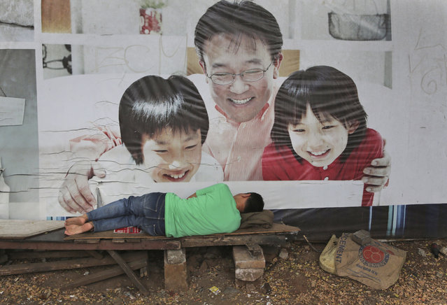 An Indonesian man takes a nap near an advertisement banner in Jakarta, Indonesia, Thursday, October 30, 2014. (Photo by Tatan Syuflana/AP Photo)