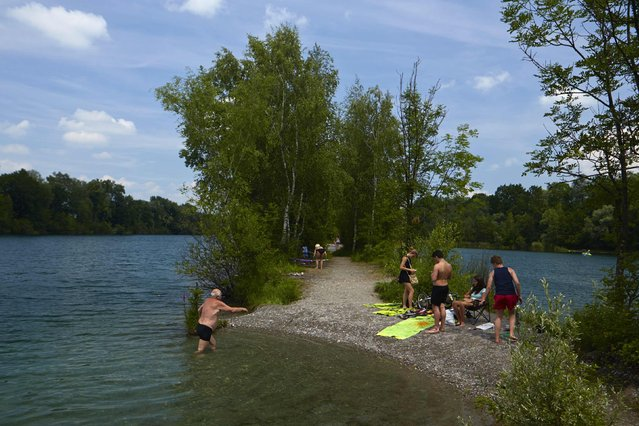 People relax near the water in the Alter Rhein at the border between Austria (R) and Switzerland in Diepoldsau May 14, 2014. (Photo by Denis Balibouse/Reuters)