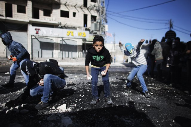 Palestinian youths throw stones towards Israeli border police during clashes at a checkpoint between the Shuafat refugee camp and Jerusalem November 7, 2014. Palestinian protesters fought with Israeli security forces in East Jerusalem and the occupied West Bank on Friday, the latest clashes in a fortnight of violence over access to Jerusalem's holiest site, known to Muslims as the Noble Sanctuary and to Jews as Temple Mount. (Photo by Finbarr O'Reilly/Reuters)