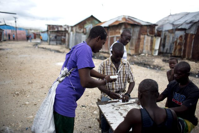 """A man carries a sack of rocks on his back, left, as he plays dominoes with friends in the Cite Soleil slum of Port-au-Prince, Haiti, Monday, November 6, 2017. The loser of a game has to wear the sack of rocks until he wins a game, when he wins the title of """"king"""" and can pass the sack of rocks to the new loser. (Photo by Dieu Nalio Chery/AP Photo)"""