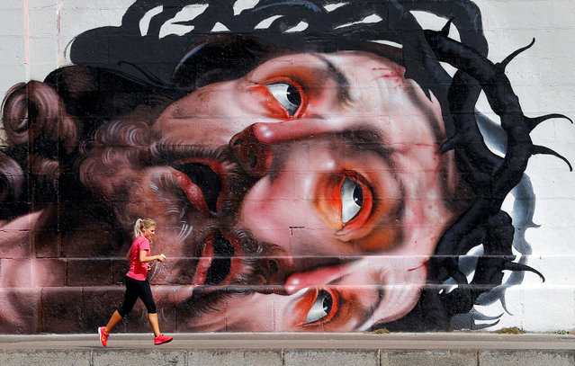 A jogger runs on the bank of Donaukanal channel in central Vienna, Austria, September 5, 2016. (Photo by Heinz-Peter Bader/Reuters)