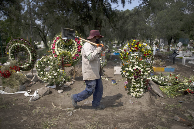 A grave digger walks in the COVID-19 section of the cemetery of San Lorenzo Tezonco Iztapalapa on the outskirts of Mexico City, Tuesday, September 1, 2020. (Photo by Marco Ugarte/AP Photo)