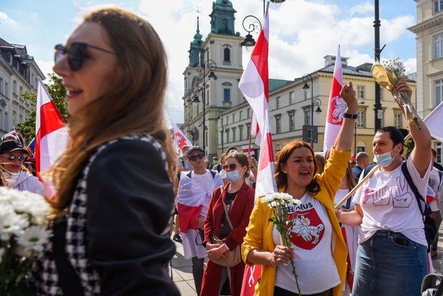 The Belarusian minority living in Poland wear face masks, hold banners and Belarus flags as they wait for the Exiled Belarus Opposition Leader Sviatlana Tsikhanouskaya at the old town on September 09, 2020 in Warsaw, Poland. Following the Belarus' disputed presidential election results, which gave victory to ruling President Alexander Lukashenko, protests emerged in the country. Thousands have been arrested and the main Presidential candidate Svetlana Tikhanovskaya fled to Lithuania. (Photo by Omar Marques/Getty Images)