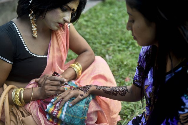 "A Bangladeshi hijra – transgender – (L) applies henna on a woman's hand as a part of the first ever nationwide program to observe ""Hijra Day"" to be held on November 10, in Dhaka on November 9, 2014. On November 10, 2013, the Bangladesh government officially recognised hijras as a separate gender in order to secure their rights, enabling them to identify their gender as ""hijra"" on all government documents, including passports. (Photo by Munir Uz Zaman/AFP Photo)"