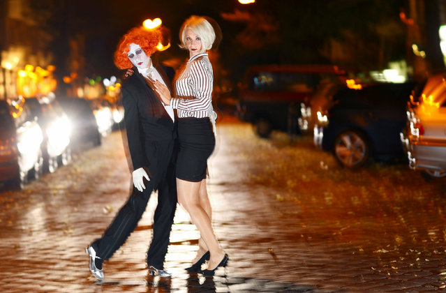 "Artist Le Pustra and organiser Else Edelstahl pose for a picture at Simon Dach Strasse, a street filled with many bars, in Berlin, Germany, August 28, 2016. Else Edelstahl organises the party series ""Boheme Sauvage"", in which people dress up in 1920s style, celebrating Berlin nightlife of a past era. (Photo by Hannibal Hanschke/Reuters)"