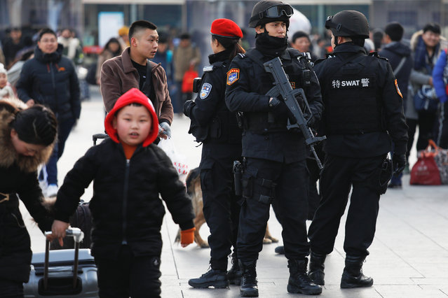 Members of a SWAT team take positions at the Beijing Railway Station as the annual Spring Festival travel rush begins ahead of the Chinese Lunar New Year, in central Beijing, China on February 1, 2018. (Photo by Damir Sagolj/Reuters)