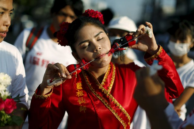 A devotee of the Chinese Ban Tha Rue shrine walks with spikes pierced through her cheeks during a procession celebrating the annual vegetarian festival in Phuket, Thailand, October 17, 2015. (Photo by Jorge Silva/Reuters)