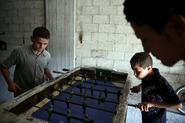 Children play table football on the last day of Eid al-Adha celebrations in the rebel held besieged town of Hamouriyeh, eastern Ghouta, near Damascus, Syria September 15, 2016. (Photo by Bassam Khabieh/Reuters)