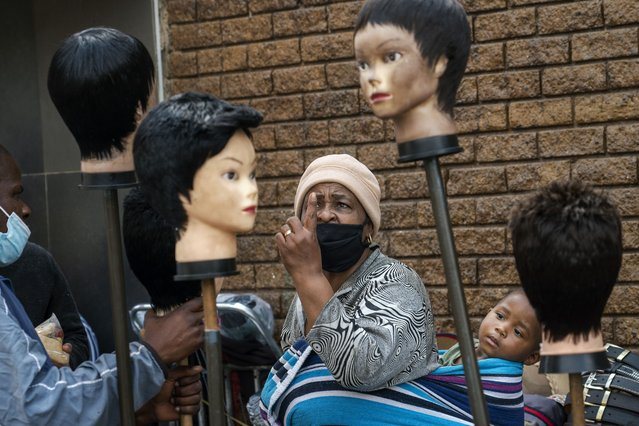 A woman carrying a child on her back looks at wigs on sale at the Baragwanath Taxi Rank in Soweto, South Africa, Wednesday, September 16, 2020. South African president Cyril Ramaphosa is scheduled to address the nation later in the day, as case numbers and death from COVID-19 hit the lowest in months. (Photo by Jerome Delay/AP Photo)