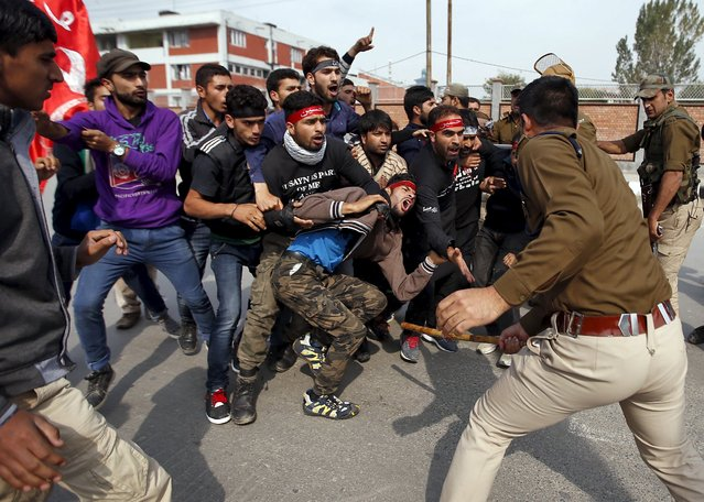 An Indian police officer wields his baton against Kashmiri Shi'ite Muslim mourners during a Muharram procession ahead of Ashura in Srinagar October 22, 2015. (Photo by Danish Ismail/Reuters)