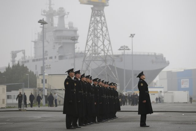 Russian sailors stand in formation in front of the Mistral-class helicopter carrier Vladivostok at the STX Les Chantiers de l'Atlantique shipyard site in Saint-Nazaire, western France, November 25, 2014. France suspended indefinitely on Tuesday delivery of the first of two Mistral helicopter carrier warships to Russia, citing conflict in eastern Ukraine where the West accuses Moscow of fomenting separatism. (Photo by Stephane Mahe/Reuters)