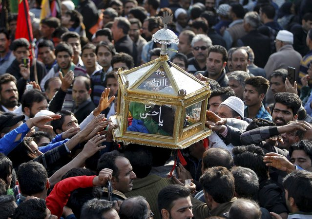 Kashmiri Shi'ite Muslim mourners touch a glass case containing a copy of the Koran during a Muharram procession ahead of Ashura in Srinagar October 21, 2015. Ashura, which falls on the 10th day of the Islamic month of Muharram, commemorates the death of Imam Hussein, grandson of Prophet Mohammad, who was killed in the 7th century battle of Kerbala. (Photo by Danish Ismail/Reuters)