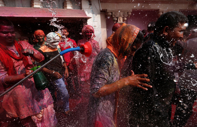Girls run for cover as boys spray colored water on them during religious religious festival of Holi inside a temple in Nandgaon village, in the state of Uttar Pradesh, India February 25, 2018. (Photo by Adnan Abidi/Reuters)