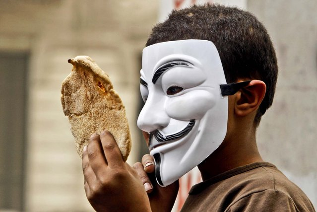 A boy wearing a Guy Fawkes Mask holds bread, a symbol of poverty, during an anti-Muslim Brotherhood demonstration in Cairo, Egypt, on March 22, 2013. (Photo by Amr Nabil/Associated Press)
