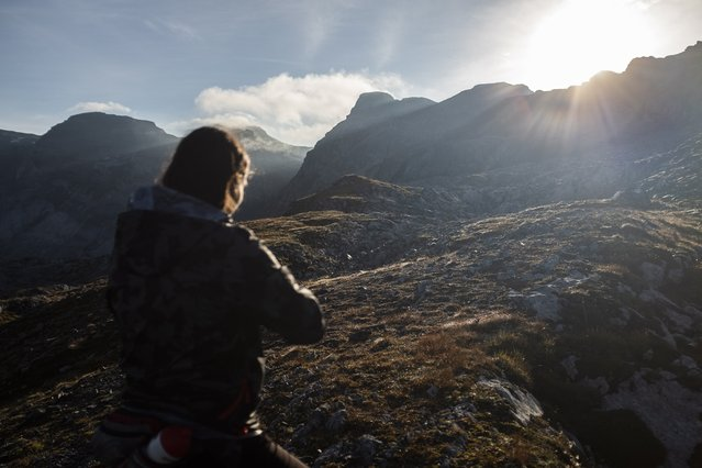 A woman looks into the sunrise while hiking on an alpine trail at Panixerpass in Elm, Switzerland, 13 September 2020. (Photo by Gian Ehrenzeller/EPA/EFE)