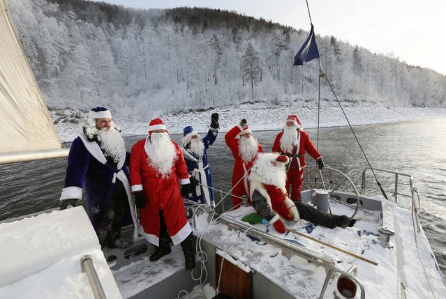 "Members of the ""Skipper"" yacht club dressed as Father Frost, the Russian equivalent of Santa Claus, greet the crew of another boat as they sail a yacht to mark the end of the sailboat season, with the air temperature at about minus 18 degrees Celsius (minus 0.4 degrees Fahrenheit), on the Yenisei River, outside Russia's Siberian city of Krasnoyarsk, November 30, 2014. (Photo by Ilya Naymushin/Reuters)"