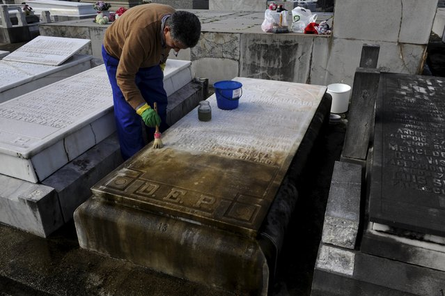 A man cleans a tomb in the municipal cemetery of La Carriona in Aviles, northern Spain, October 29, 2015. (Photo by Eloy Alonso/Reuters)