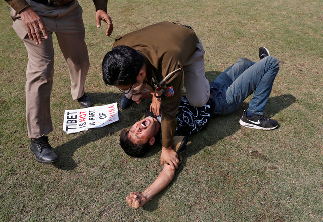 A Tibetan reacts as he is detained by police during a protest held to mark the 59th anniversary of the Tibetan uprising against Chinese rule, outside the Chinese embassy in New Delhi, India, March 9, 2018. (Photo by Cathal McNaughton/Reuters)