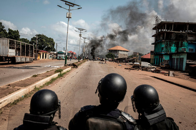 Police officers look on as protesters block the road with burning tyres and wood, during a mass protest the morning after preliminary results were released for five communes in Conakry on October 21, 2020. African monitors said on October 20, 2020, that Guinea's weekend election was conducted properly, but the political opposition to incumbent Alpha Conde, which has already claimed victory, dismissed it as fraudulent. (Photo by John Wessels/AFP Photo)