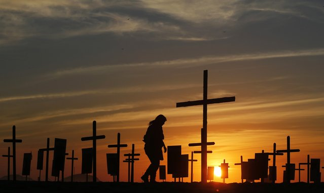 A police officer walks among crosses planted by the NGO Rio de Paz (Peace Rio) on Copacabana beach, in memory of police officers killed in Rio de Janeiro December 9, 2014. Rio de Paz placed 152 black crosses symbolising the same number of police officers killed in the last two years in Rio de Janeiro, according to NGO. (Photo by Sergio Moraes/Reuters)