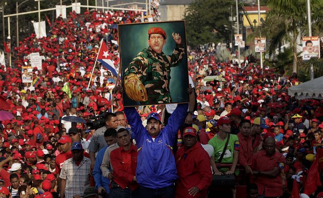 Venezuela's acting President Nicolas Maduro holds up a painting of Hugo Chavez during a campaign rally in Catia La Mar, on April 9, 2013. Maduro, the hand-picked successor of Chavez, is running for president against opposition candidate Henrique Capriles on April 14. (Photo by Ariana Cubillos/Associated Press)