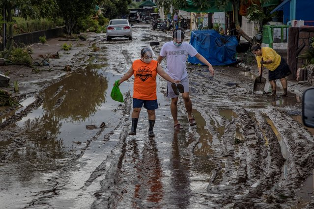 Residents walk along a road filled with mud left behind by flashfloods caused by Typhoon Goni on November 2, 2020 in Batangas city, south of Manila, Philippines. Super Typhoon Goni, this year's most powerful storm in the world, hit the Philippines with wind gusts of up to 190 miles per hour on November 1. The typhoon left at least ten people killed. (Photo by Ezra Acayan/Getty Images)