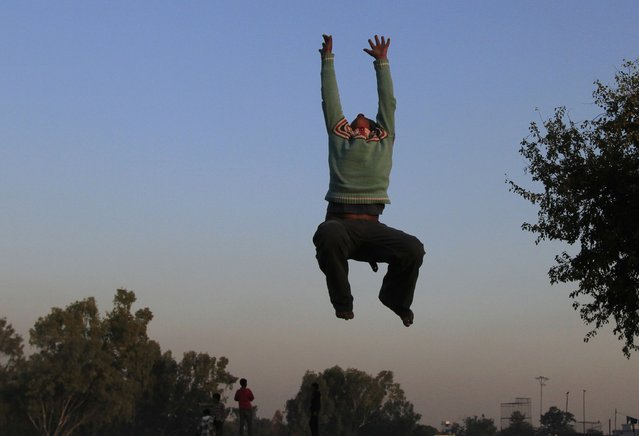 A boy jumps on a trampoline as he plays at a Christian slum in Islamabad December 10, 2014. (Photo by Faisal Mahmood/Reuters)